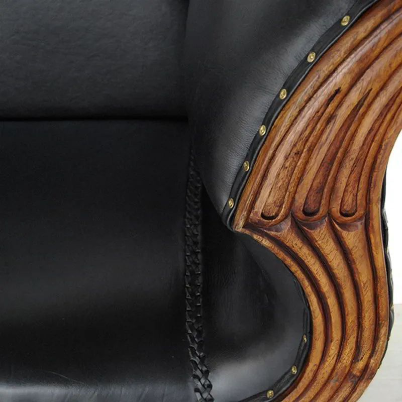 Wood carving detail on the frame of Teak leather loveseat